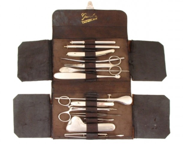 A 19th century French surgical leather kit with knife and needle, artery forceps, curved scissors, curette, trocar, director, blunt needle, thermometer, caustic stick holder,  toothed forceps and two plain forceps. (Phisick Medical Antiques)