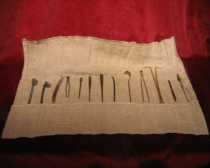 A replica of Roman surgical instruments in a cloth roll, AD50. 13 instruments made of brass and steel. (The Old Operating Theatre Museum)