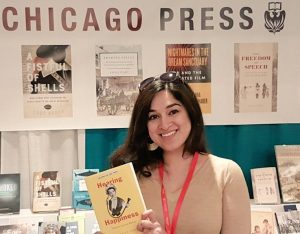 The author, a dark haired Indian woman, stands and smiles. She is holding a yellow book and standing in front of a book exhibit