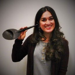 An indian woman standing and smiling at the camera. She has long curly hair and is wearing a grey top and a brown cardigan. In her right hand, she is holding a large black ear trumpet, with the earpiece positioned in her right ear.