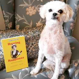 A small white dog sitting on a sofa. Next to her is a book with a yellow cover and the title Hearing Happiness.