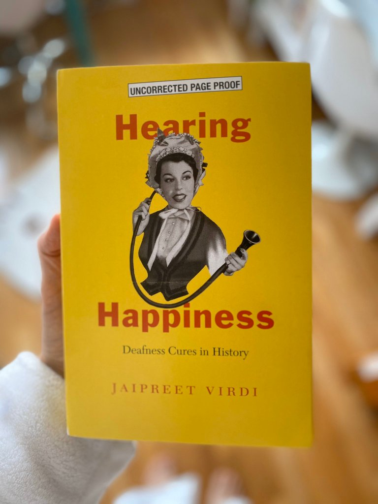 A woman's hand holding the yellow book of Hearing Happiness against a blurry background.