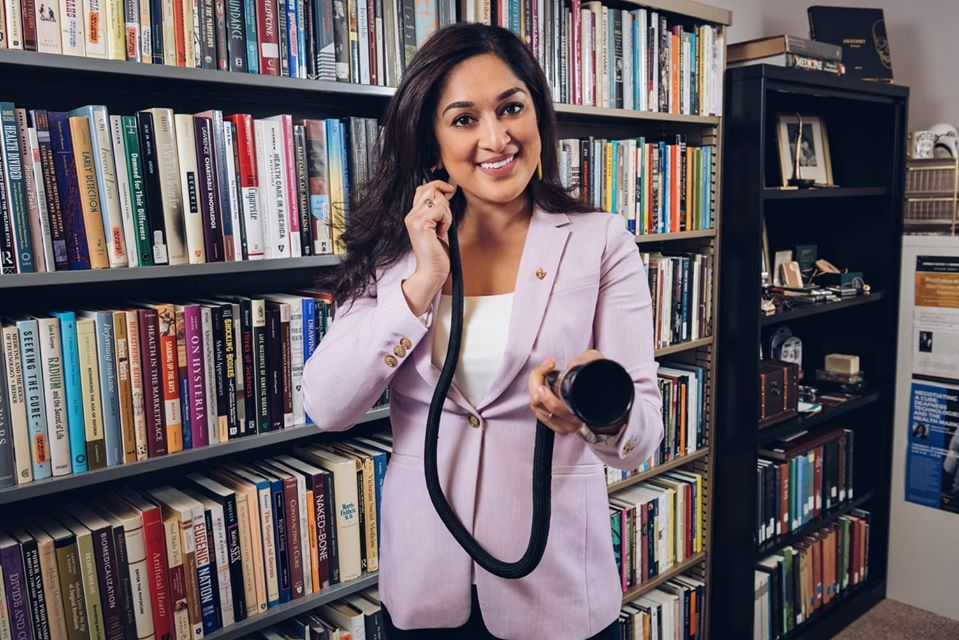 The author wearing a purple blazer and standing in front of a wall of books. She is holding a conversation tube and smiling