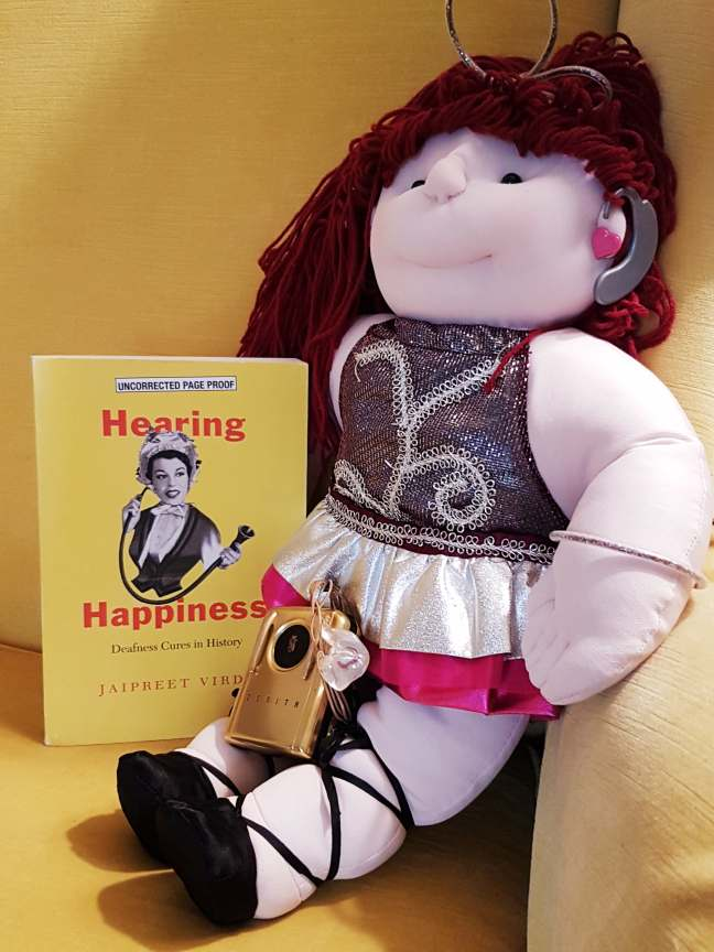 A stuffed doll dressed as a ballerina and wearing a hearing aid is placed next to a yellow book with the title Hearing Happiness. On the doll's lap is a golden 1950s hearing aid.