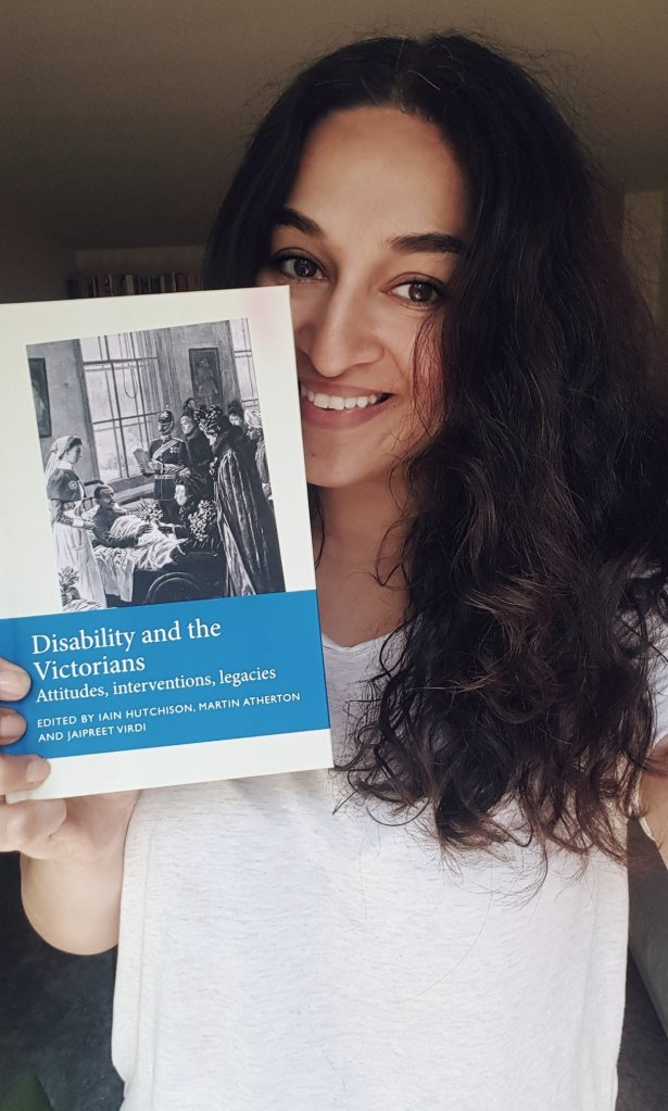 An indian woman with shoulder length curly hair smiling and holding a copy of Disability and the Victorians.