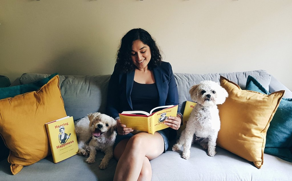 Jai sits in the middle of a grey sofa smiling and looking at her copy of Hearing Happiness. to her right, Benny, a small white dog with one eye, is lying down and leaning against her leg. He is smiling. To Jai's right is Lizzie, a small white dog who is sitting up with a serious expression. There are copies of the book next to both dogs.