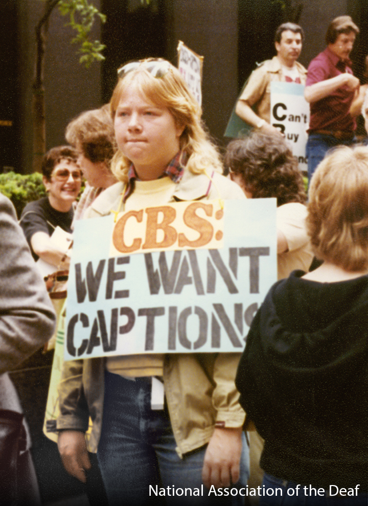 """A white woman standing amongst a crowd. She is wearing a sign that says """"CBS: WE WANT CAPTIONS"""""""